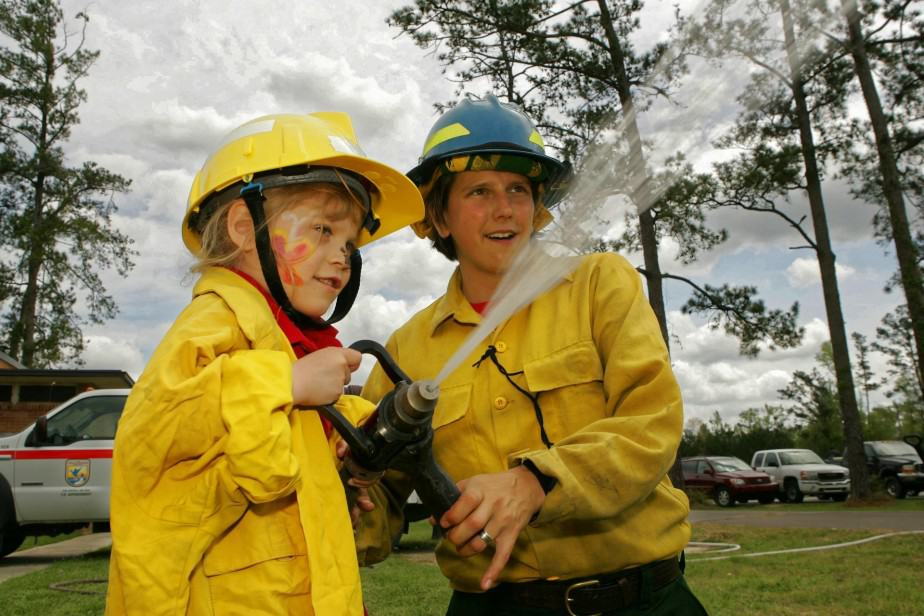 firefighter spraying water with child