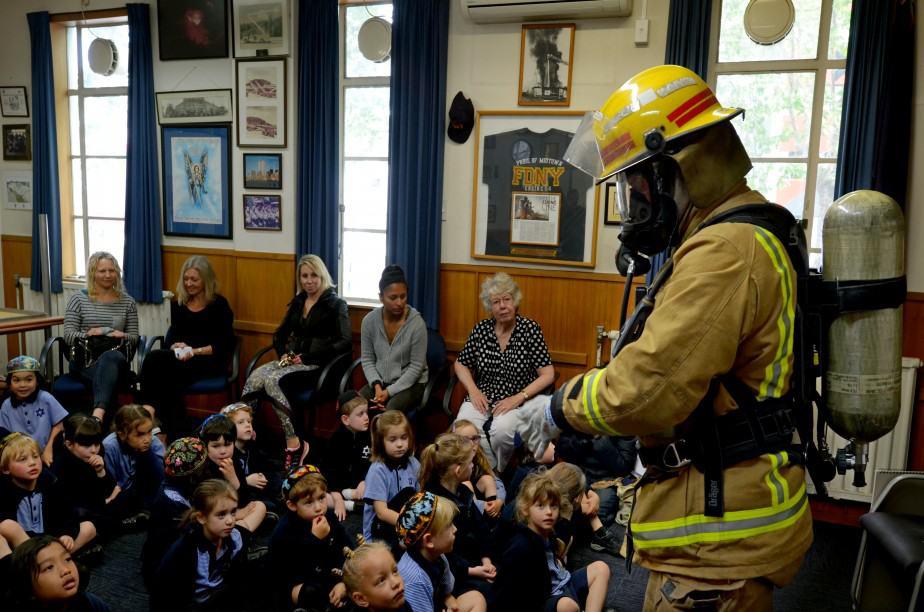 Firefighter speaking to classroom of children